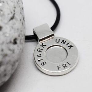 runt silversmycke i läderrem med texten STARK, UNIK, FRI på vit bakgrund med sten bredvid