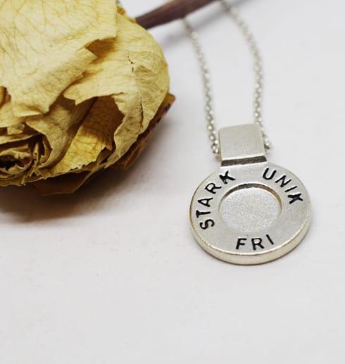 runt silversmycke i kedja med texten STARK, UNIK, FRI på vit bakgrund med gul ros bredvid