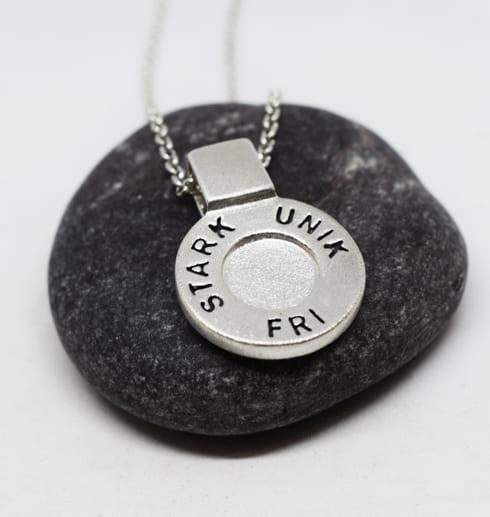runt silversmycke i kedja med texten STARK, UNIK, FRI på mörkgrå sten