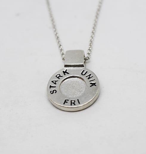 runt silversmycke i kedja med texten STARK, UNIK, FRI på vit bakgrund