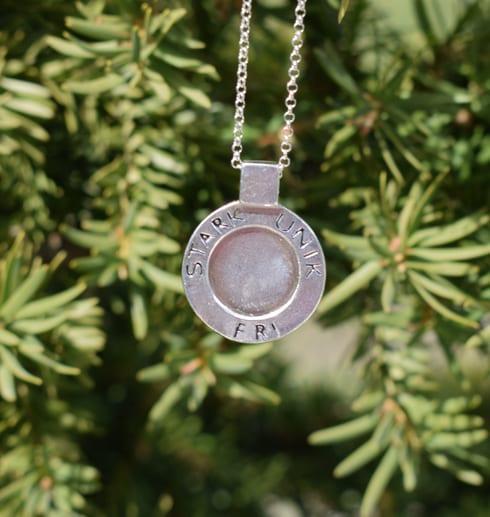 runt silversmycke med text hängande utomhus framför enbuske