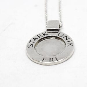 runt silversmycke med texten STARK, UNIK, FRI på vit bakgrund