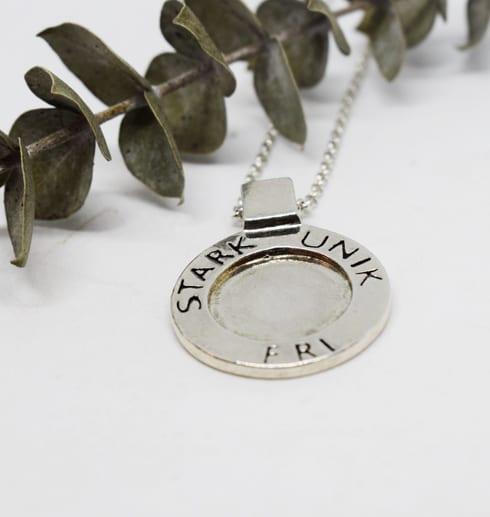 silverhalsband i rund form med texten STARK, UNIK, FRI på vit bakgrund med grön kvist bredvid
