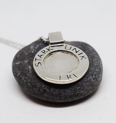 runt silversmycke med texten STARK, UNIK, FRI på grå sten