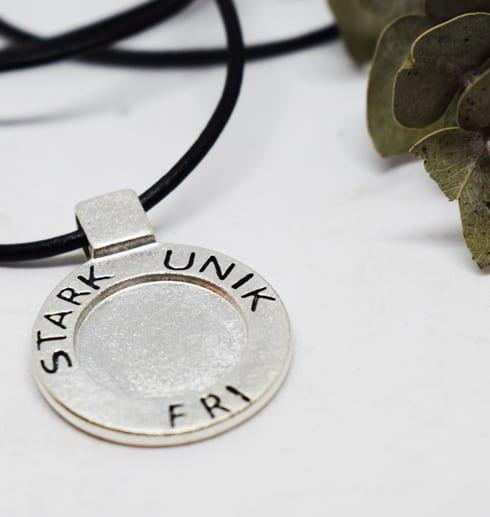 runt silversmycke i läderrem med texten STARK, UNIK, FRI på vit botten med grön kvist bredvid