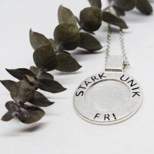 silverhalsband med texten STRAK, UNIK, FRI med vit bakgrund och grön kvist bredvid