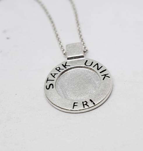 silverhalsband med texten STRAK, UNIK, FRI med vit bakgrund