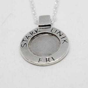 runt silvermyce med texten STARK, UNIK, FRI mot vit bakgrund