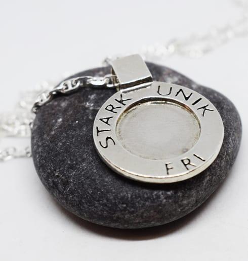 runt silverhalsband med texten STARK, UNIK, FRI liggande på en mörkgrå sten