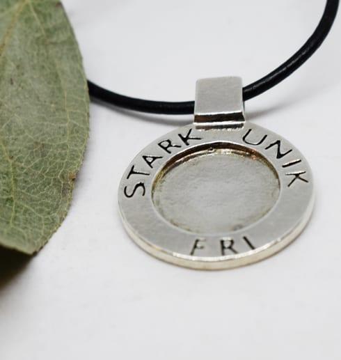 silversmycke med texten STARK, UNIK och FRI i läderrem med grönt löv bredvid