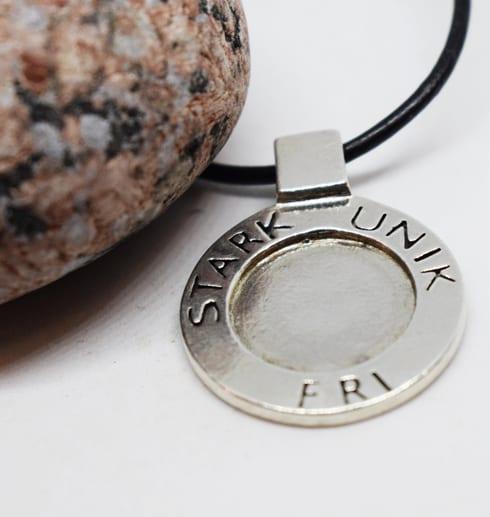 silversmycke i läderrem med text på vit botten med röd sten