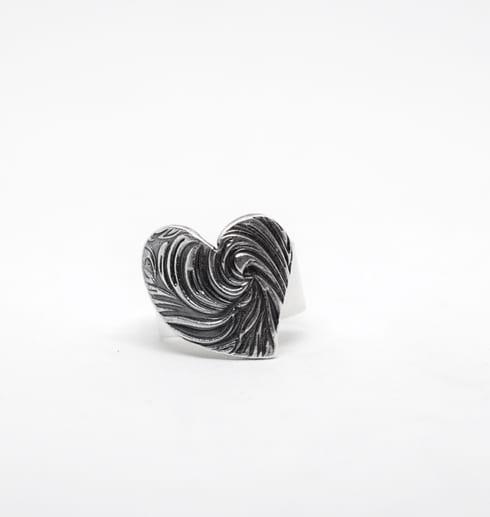 silverring med mönstrat hjärta på vit bakgrund