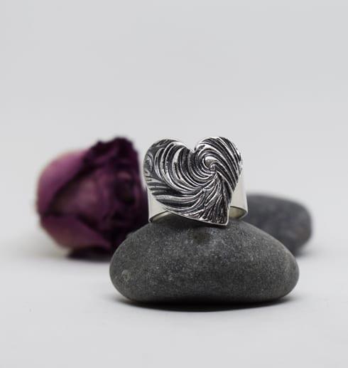 silverring med mönstrat hjärta på stenar med ros bakom