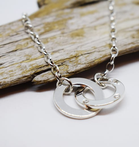 armband med ringar på vit bakgrund med trädbit bakom