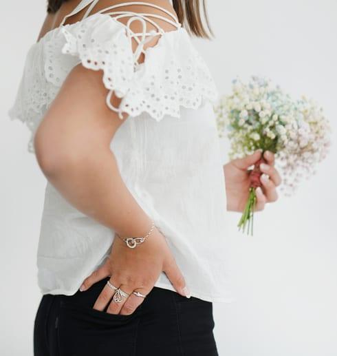 Blicka med svarta byxor och vit blus och blommor i handen med armband runt handleden