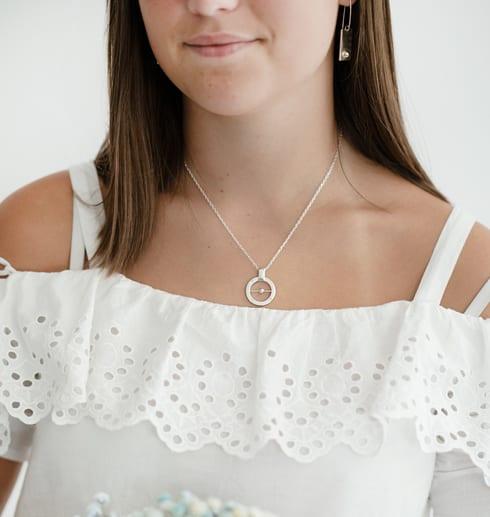 flicka med vit blus och halsband runt halsen
