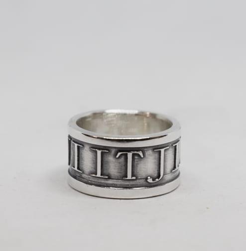 bred silverring med upphöjd text och vit bakgrund