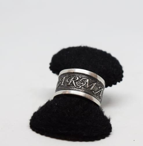 bred silverring med svartoxiderad bakgrund och upphöjd text på svart sammetshållare