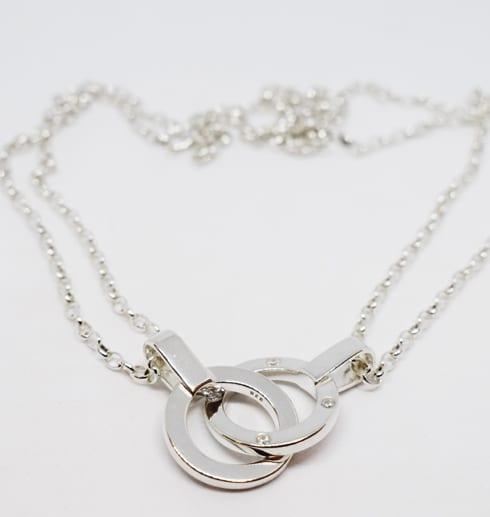silverhalsband med dubbla ringar mot vit bakgrund
