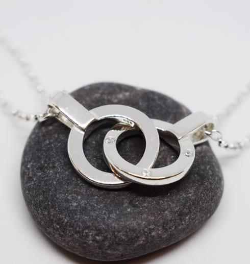 dubbla ringar i halsband i silver på grå sten