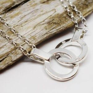 halsband med dubbla ringar i silver med träbit och vit bakgrund
