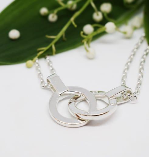 silverhalsband med dubbla ringar mot vit bakgrund och liljekonvaljer