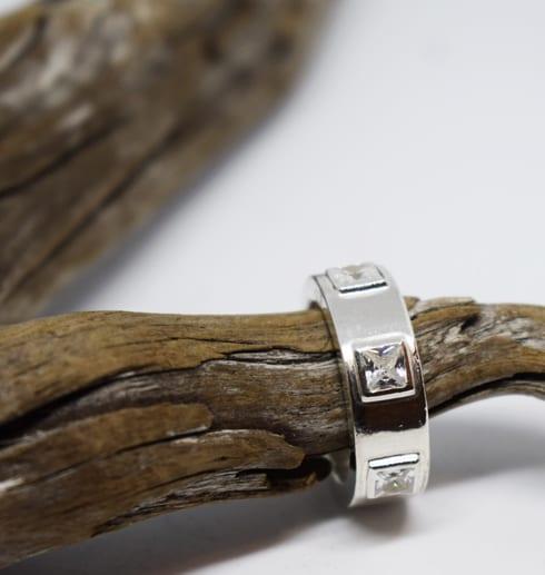 silverring med kvadratiska stenar på trädgren