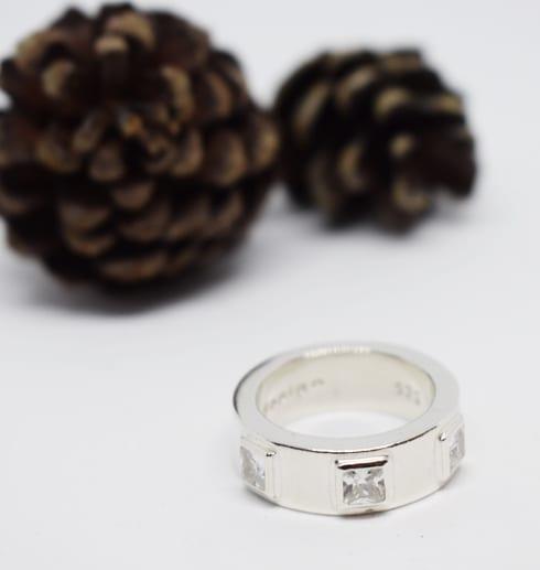 silverring med kvadratiska stenar på vit botten med kottar i bakgrunden