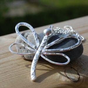 trollslända i silver på sten på trä utomhus