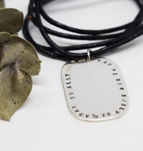 ovalt silversmycke med text i svart läderhalsband på vit bakgrund med grön kvist bredvid