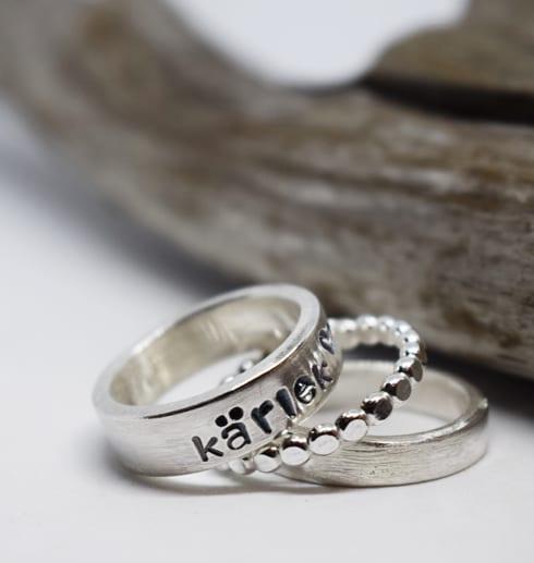tre silverringar på vit botten med träbit bakom