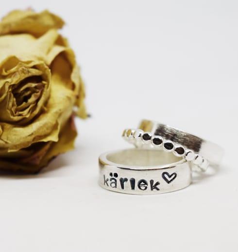 Tre silverringar en med texten kärlek på vit botten med gul sten