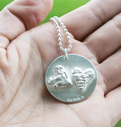 silverhalsband med hjärtan i handflata utomhus