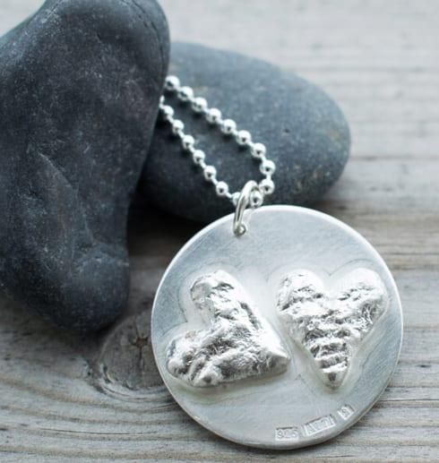 runt silversmycke med hjärtan på grå stenar