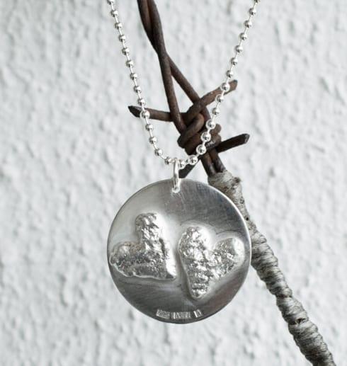 silverhalsband i forma av en rund platta med två hjärtan utomhus på taggtrådshjärta