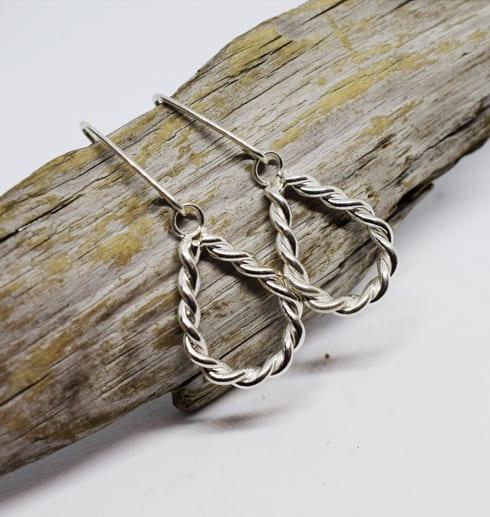 tvinnade silvertrådsörhängen på träbit