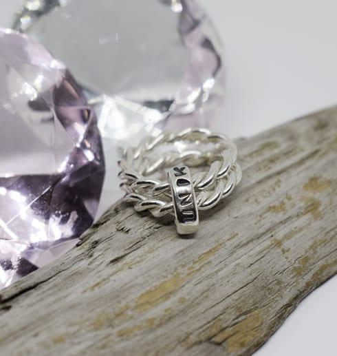silverring med texten unik på träbit med träbit och rosa diamant