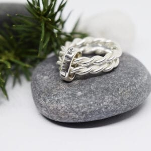 silverring med texten unik på grå sten med grankvist