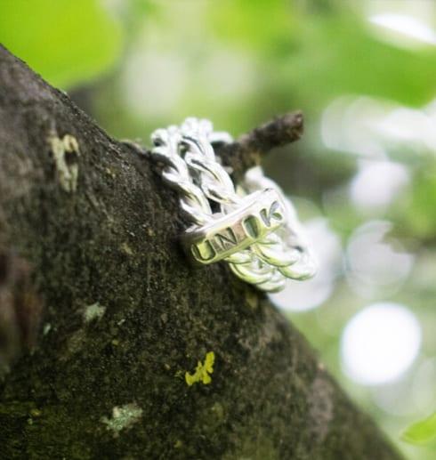 silverring med texten UNIK på träd utomhus