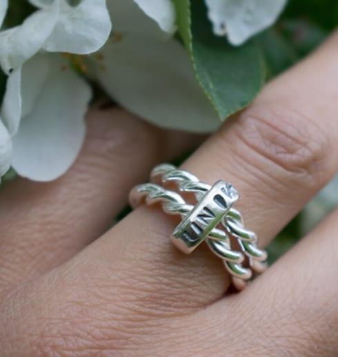 silverring med texten unik på finger med blomma utomhus