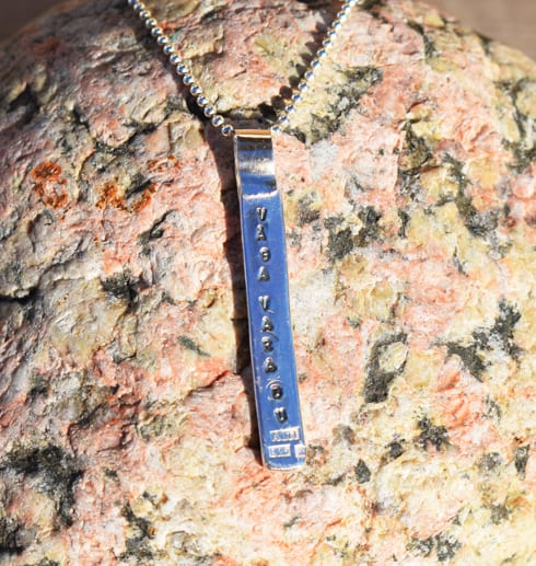 silversmycke med text på röd sten utomhus