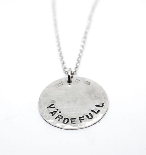 silverhalsband med texten VÄRDEFULL på vit bakgrund