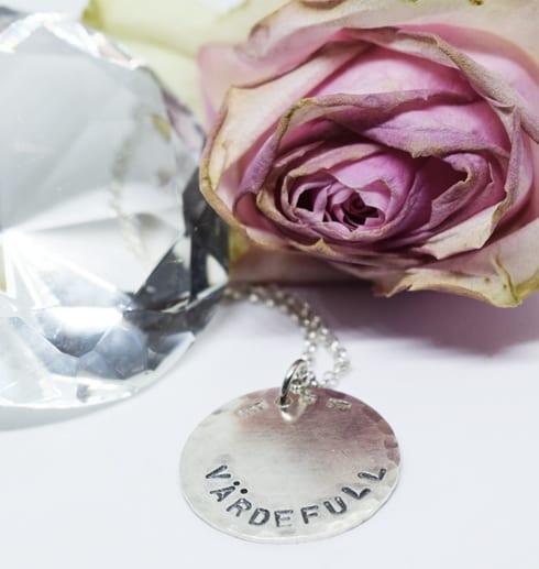 silverhalsband med texten VÄRDEFULL med ros och diamant bredvid