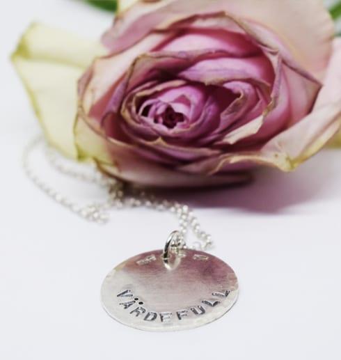 silverhalsband med texten VÄRDEFULL på vit botten med rosa ros bakom