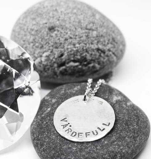 silverhalsband med texten VÄRDEFULL på stenar med diamant bredvid