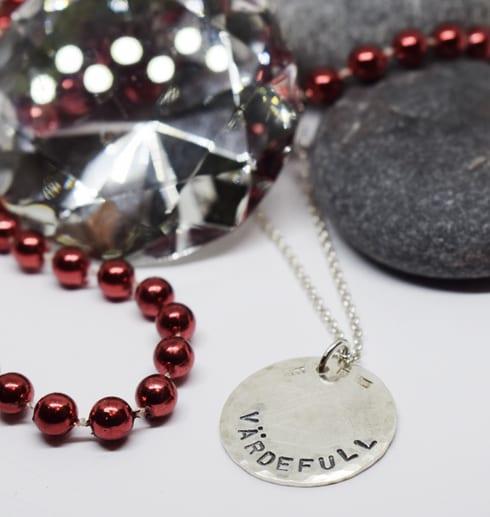 silverhalsband med tetxten VÄRDEFUL med stenar, diamant och röda kulor