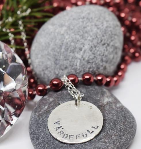 silverhalsband med texten VÄRDEFULL på stenar med röda rulor