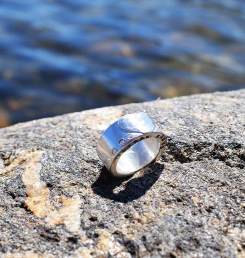 grov silverring med hjärta och text på klippa vid havet