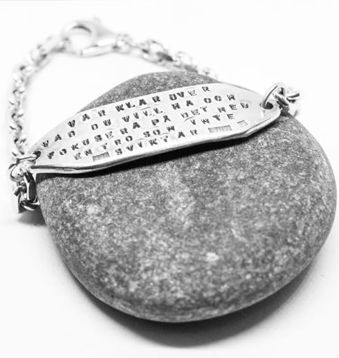 silverarmband med lång text på grå sten