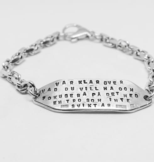 silverarmband med lång text på vit bakgrund